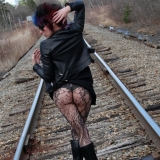 Goth babe Sabrina shows off her perfect round ass in black lace with a matching thong outdoors on the railroad tracks