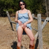 Horny tease Sabrina has no panties on under her dress as she flashes her pussy in a country field