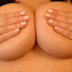 Krissy squeezes her huge perfect 34D tits together