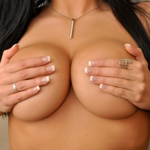 Krissy plays with her huge juicy boobs after freeing them from her corset