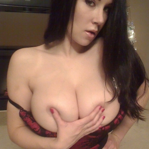 Busty babe Sweet Krissy teases with her big juicy tits in a red and black lace corset
