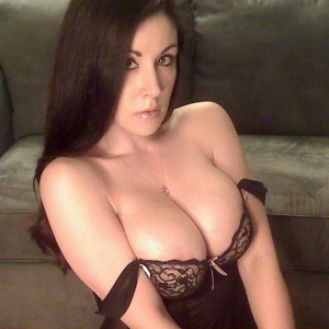 Busty babe Sweet Krissy squeezes her big juicy tits together in a sexy lace and sheer lingerie outfit