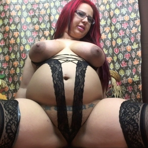 Pregnant pornstar Georgia Peach shows off her swollen belly and big tits in a little black lace teddy